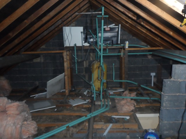 Hot water system in loft before new boiler installation